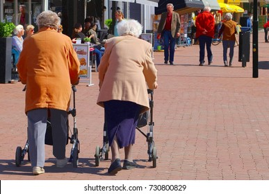 SOEST, NETHERLANDS - May 21, 2016. Two elderly women are walking together with rollators and shopper bags at a pedestrian path in Dutch shopping street with stores and shops. Aging population.