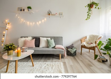Sofa, coffee table and wicker chair in living room styled scandinavian