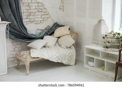 sofa with cushions. wall with bricks and grey curtain