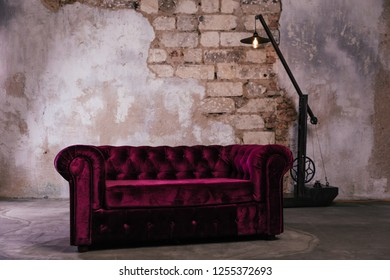 sofa in the interior in the style of loft, raspberry sofa, bright pink sofa in the interior with a stone wall