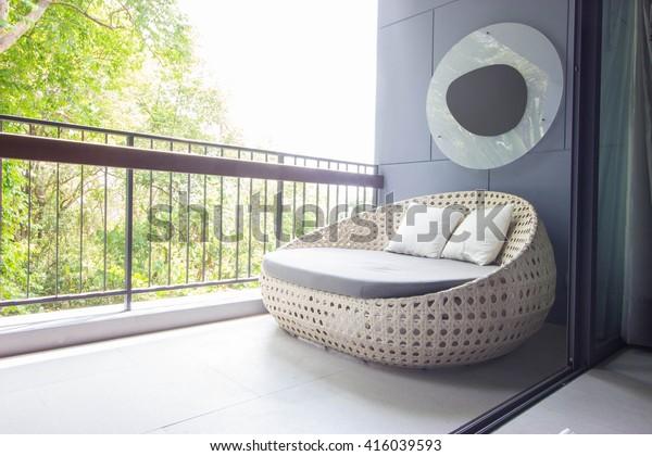 Sofa auf dem Balkon mit Gartenblick.