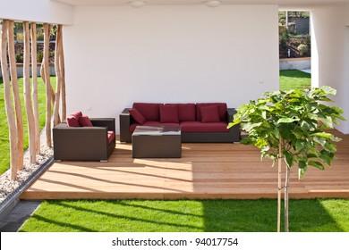sofa on modern wooden terrace with garden