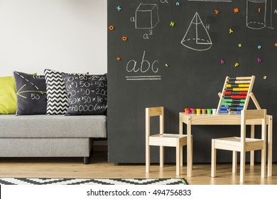 Sofa standing next to a chalkboard wall with geometrical figures, in the foreground small table and wooden chairs