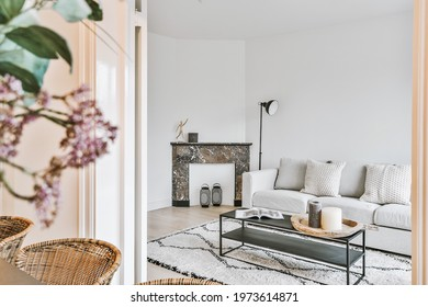 Sofa and table with decorations placed near marble fireplace behind doorway of dining room in elegant apartment