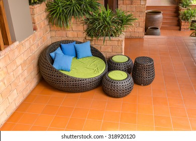 sofa weave Rattan stick chair with blue pillows on orange tile and old brick wall
