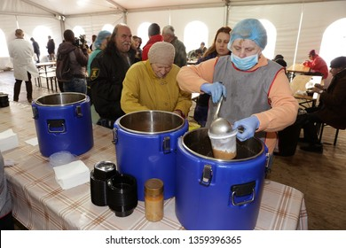 Sofia, Bulgaria - 14 February 2019: ?mployee in a kitchen for poor and homeless people pours warm soups in containers for visitors of the kitchen.