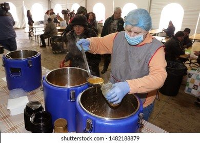 Sofia, Bulgaria - 14 February 2019: Employee in a kitchen for poor and homeless people pours warm soups in containers for visitors of the kitchen.