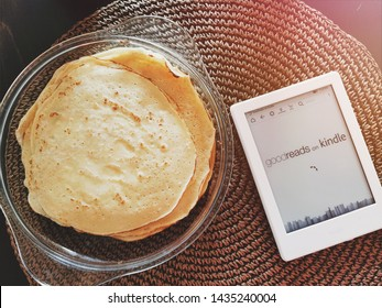 Sofia, Bulgaria - 26 June 2019 - Relaxing Reading on a Kindle e book reader, loading Amazon goodreads catalog next to a plate of fresh homemade pancakes