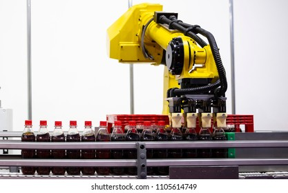 Sofia, Bulgaria - 28 March 2018: Yellow robotic arm arranges plastic soda bottles in a packing case. Automatic industrial machinery equipment.