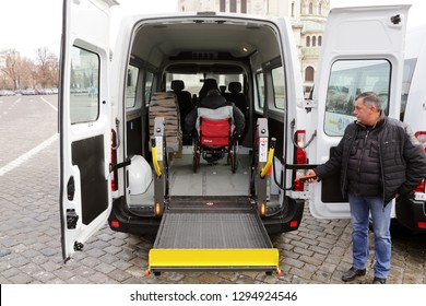Sofia, Bulgaria - 7 January 2019: Driver assists a physically disabled man in a wheelchair to get in a minibus with stowed wheelchair ramp.