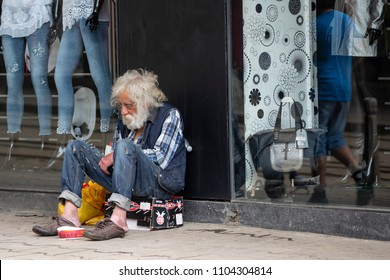 Sofia, Bulgaria - 7 May, 2018: Homeless old man with long white beard begs for money in front of clothes shop. Ten years after joining the EU Bulgaria is still the poorest country in the union.