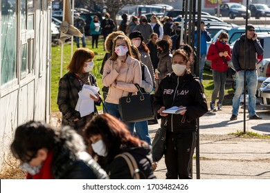 Sofia, Bulgaria - April 8, 2020: People wearing face masks in an attempt to prevent the spread of coronavirus disease COVID-19 wait in line in front of an office of the labor bureau.