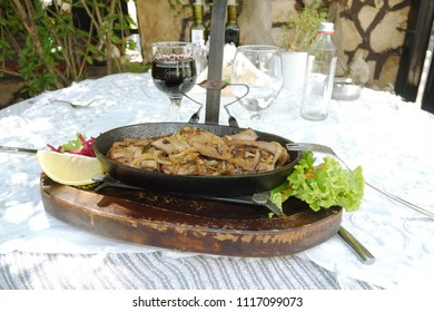 SOFIA, BULGARIA - AUGUST 02, 2017: a liver dish with onions in a pan on the table of one of the best traditional cuisine restaurants in Sofia
