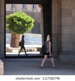 SOFIA, BULGARIA - AUGUST 02, 2017: young woman in summer casual wear walking and looks at her own reflection in the mirror glass windows