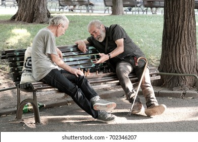 SOFIA, BULGARIA - AUGUST 02, 2017: two middle-aged men sitting on a bench and playing a match of chess in a city garden of Sofia downtown