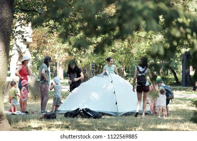 SOFIA, BULGARIA - AUGUST 04, 2017: women teaching to children how to pitch a tent in a Sofia Park