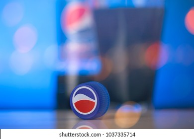 SOFIA, BULGARIA - FEBRUARY 28, 2018:Pepsi Cola Cap over the blue background and colorfull bokeh.Pepsi is a carbonated soft drink that is produced and manufactured by PepsiCo.