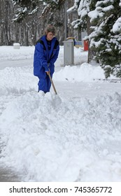Sofia, Bulgaria - Jan 7, 2013: A person woman cleans the alleys in the park from snow after a big snowstorm in the city, cleans sidewalk from the snow