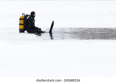 Sofia, Bulgaria - January 6, 2015: Two divers are swimming into the frozen lake waters before Bulgarian men jump for a wooden cross at Epiphany day celebration in Sofia.