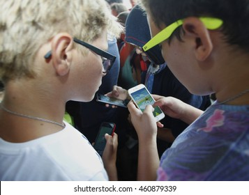 Sofia, Bulgaria - July 30, 2016: Children playing with their mobile phones to the Pokemon game