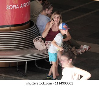 SOFIA, BULGARIA - JULY 31, 2017: mature woman is smiling at mobile phone  sitting in a metro station to Sofia airport