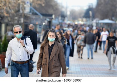Sofia, Bulgaria - MAR 13 2020: A young woman and an older man are walking on Vitosha street. Few hours after that was announced State of Emergency in the country because of the corona virus outbreak.