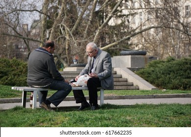 Sofia, Bulgaria - March 04, 2017 - Two adult males lunch on a park bench