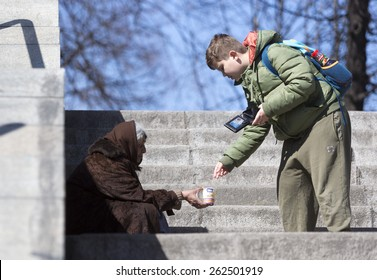 Sofia, Bulgaria - March 17, 2015: A boy is giving money to a homeless female beggar who is begging at the subway underpass stairs in the center of Sofia.