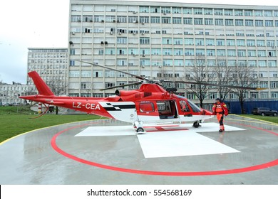 Sofia, Bulgaria - March 23, 2016: A doctor boarded a helicopter medical emergency, which is perched on the ground before takeoff administrative building