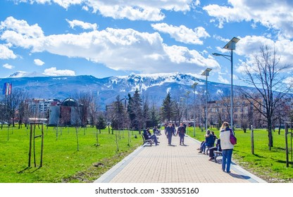 SOFIA, BULGARIA, MARCH 25, 2015: young bulgarians are walking through park in student city in sofia with vitosha mountain on background.