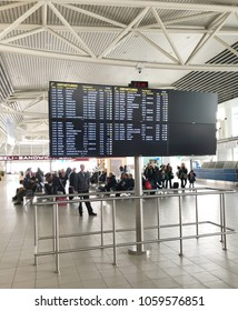 """Sofia, Bulgaria - March 25, 2018: Passengers looking at the flight information board. """"Sofia Airport"""" EAD is a licensed airport operator of the largest international airport in Bulgaria."""
