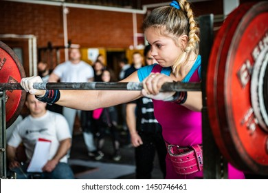 Sofia, Bulgaria - Mart 23, 2019: Portrait of beautiful young Bulgarian power-lifter girl who is making successful squat attempt at Bulgarian National Powerlifting Championship Competition.