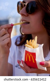 SOFIA, BULGARIA - MAY 08, 2017: Young woman eating fries and hamburgers in a McDonald's restaurant. Illustrative editorial.