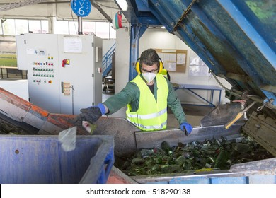Sofia, Bulgaria - May 26, 2016: Glass waste worker is recycling glass bottles in a recycling facility. Different glass packaging bottle waste. Glass waste management.