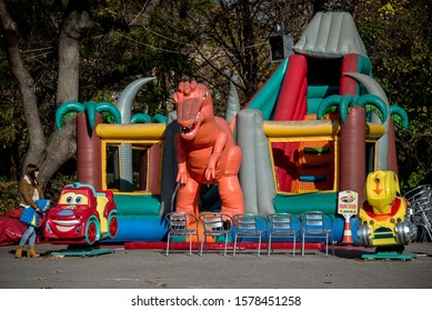 Sofia, Bulgaria - November 20, 2015: Kids park attractions, closed for the autumn season with a woman watching them - inflatable bouncy castles, an inflatable dinosaur, coin-operated rocking cars, etc