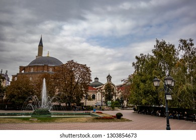 SOFIA, BULGARIA - OCTOBER 14, 2018: Many people enjoy sprinkling water of fountains in Banski Square in the Bulgarian capital. Moody cloudy sky autumn day. View from the staircase of History Museum