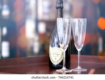 SOFIA, BULGARIA - OCTOBER 29, 2017: Dom Perignon Vintage 2006 champagne bottle and two glass, lights and bokeh from colorfull bar light