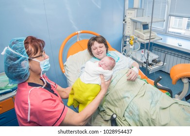 Sofia, Bulgaria,January19, 2018 : Woman holds her baby for first time after gave birth in a hospital delivery room