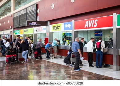 SOFIA REINA AIRPORT, TENERIFE, SPAIN - CIRCA DEC, 2015: Stands of car rental companies are at the south international airport of Tenerife island. Passengers stand in queue for vehicles hire