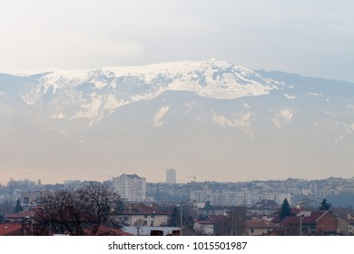 Sofia, Sofia-city / Bulgaria - February 02 2018: Light foggy air pollution over the city with snowy Vitosha mountain in the blurred background, showing levels of particulate matter in the atmosphere