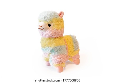 Soft alpaca plushie doll alpaca toy. Object isolated on white background with shadow reflection. The concept of gifts for the holidays. Toy in the shape of an animal. Side wiew