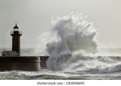Soft backlit big stormy wave splash against pier and lighthouse in a sunny day.