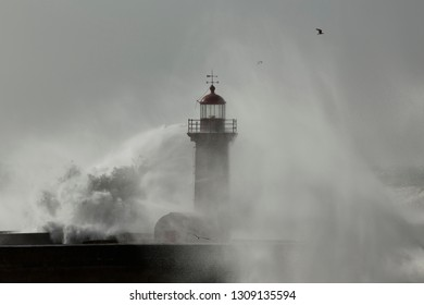 Soft backlit spray from a big stormy sea wave splash. Douro river mouth old pier and lighthouse, Porto, Portugal.