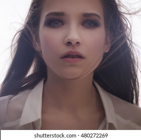 Soft beauty portrait of young sensual woman with long flying hair, clear pure skin and natural make-up. Sad and desperate emotions, deep eyes. Looking in front of camera, isolated on white.