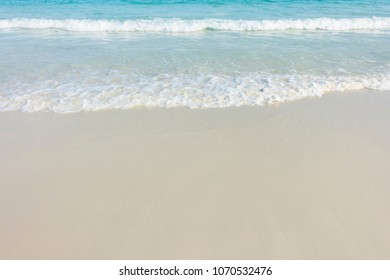 Soft blue ocean wave on sandy beach background