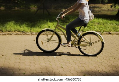 Soft and blur conception and Motion blur. Young girl riding on bicycle in the park by road at summertime