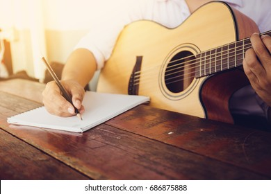 soft and blur focus.song writer holding pencil compose a song.musician playing acoustic guitar.empty space for text.concept for live music festival.Instrument on stage,abstract musical background.