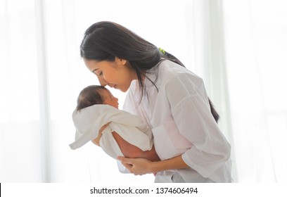 Soft blurred image of white shirt Asian mother is kissing sleeping newborn baby in bedroom in front of glass windows with white curtain to show love and family bonding.