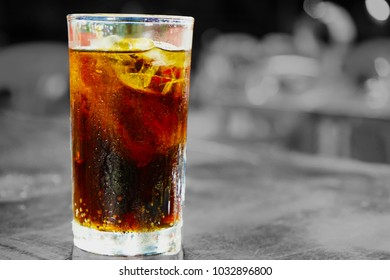 Soft and blurry image,Glass with cola and ice on a wooden table and gray background