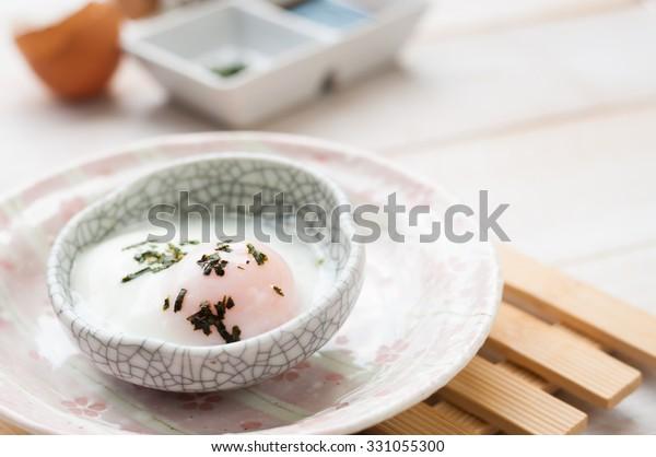 木のテーブルの上に朝食にゆで卵、日本の温泉卵